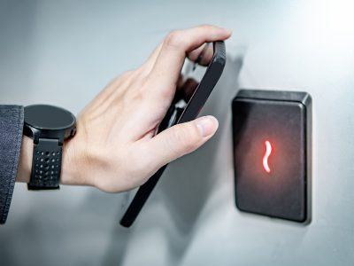 Male hand using smartphone for sensor scanning. Infrared sensor technology for automatic door access and security.