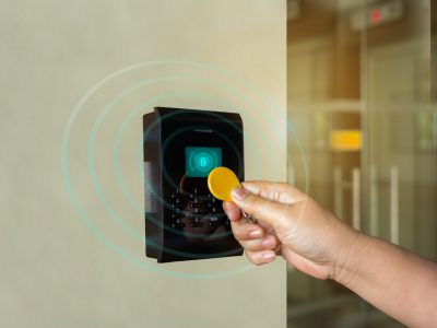 A door access control system. young person holding a key card to lock and unlock door to entry building is security system.