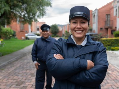 Team of Latin American security guards looking happy working at a gated community and looking at the camera smiling - safety concepts