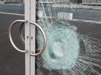 Broken glass door panel with smashed area. Shattered window on business entrance of an office building facade cracked and damaged by vandalism. The doubled glass pane is silvered on the back reflecting the cracks and sidewalk.