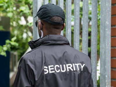 Rear View Of A Male Security Guard Wearing Black Uniform